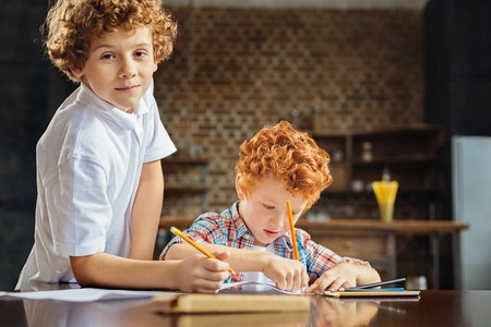 Curly haired brothers drawing together Stock Photo