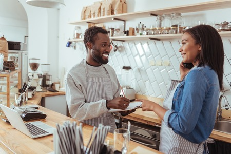 Smiling barista dictating her colleague list of necessary supplies