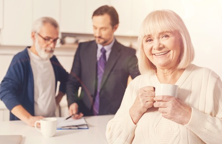 financial planning married: Cheerful retired woman drinking tea Stock Photo