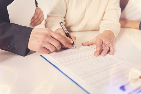 financial planning married: Pleasant elderly woman signing papers Stock Photo