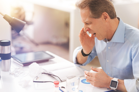 Mature sick man coughing in the office Stock Photo