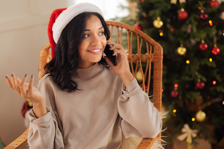 Gorgeous woman in Santa hat talking on the phone Stock Photo