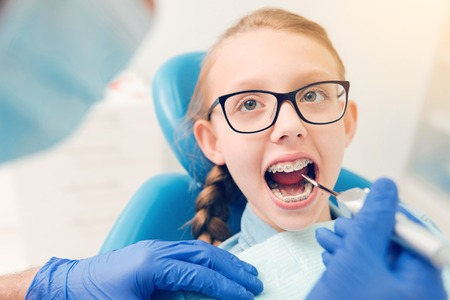 Smart little girl visiting dental professional
