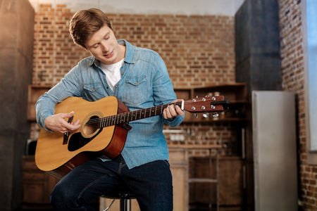 Pleasant young man playing guitar