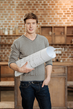 Charming man posing with a blueprint in studio