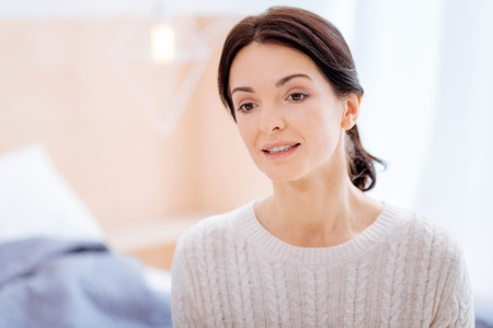 Calm young woman in warm sweater sitting in her room
