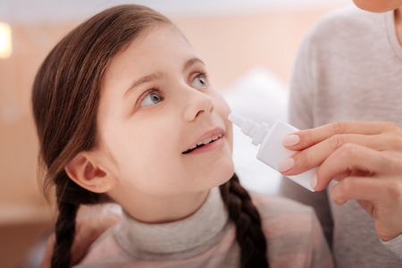 Curious recovering child with nasal drops Stock Photo