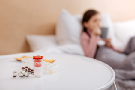 Colorful pills being placed in small boxes Stock Photo