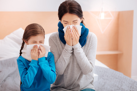 Ill mother and daughter sneezing together