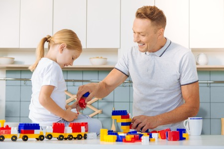 Delighted positive man having fun with his daughter Stock Photo