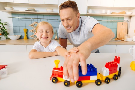 Happy positive man holding a toy train Stock Photo