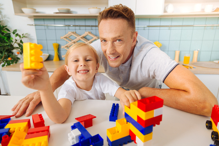 Delighted blonde girl playing with toys Stock Photo