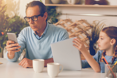 Upset daughter looking at father absorbed in work