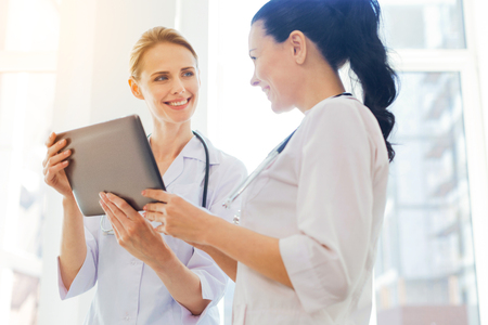 Vriendschappelijke artsen die terwijl het gebruiken van tabletcomputer op het werk glimlachen