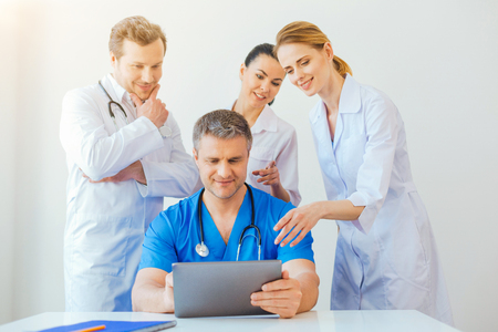 Friendly medical professional looking at laptop and smiling Stock Photo