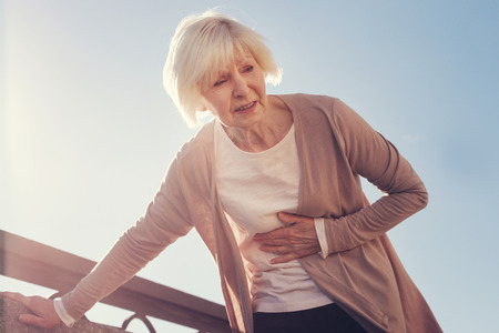 Senior woman suffering from pain in subcostal area Stock Photo