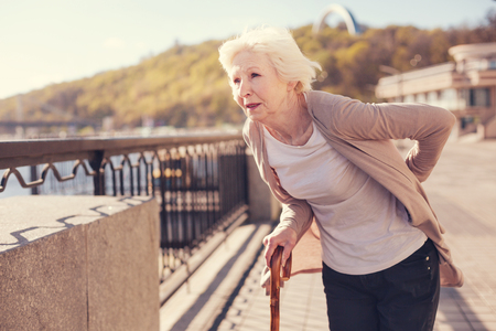 Pleasant senior woman suffering from lower back pain