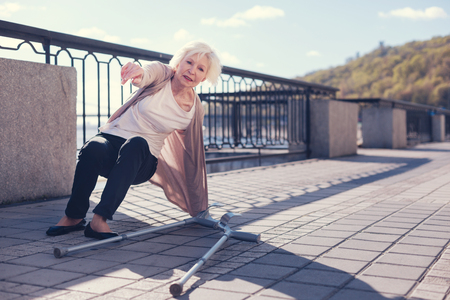 Elderly woman trying to get up after falling down Stock Photo