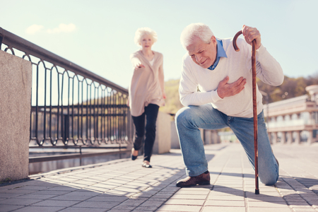 Senior man having a heart attack in the street Stock Photo