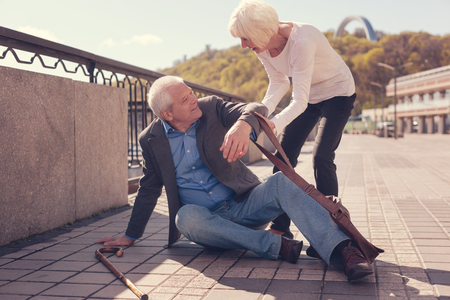 Courteous senior lady helping a passer-by get up