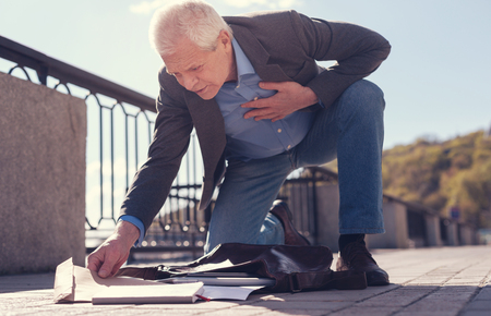Senior man with sore heart gathering his scattered belongings