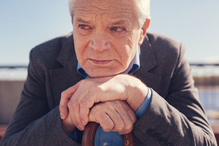 Close up of depressed senior man resting chin on hands