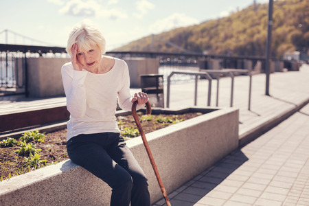 Excruciating pain. Petite senior woman sitting with a cane on a concrete edge of a flower bed and suffering from a splitting headache while pressing her hand to the temple Stock Photo