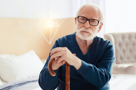 Attentive pensioner posing on camera Stock Photo