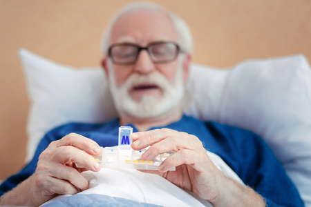 Attentive bearded man taking medicine Stock Photo