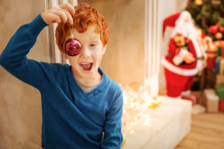 Funny redhead boy making funny faces with christmas decorative ball