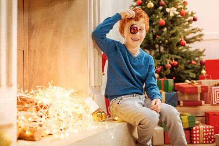 Excited ginger boy playing with decorative ball next to fireplace Stock Photo