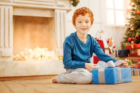 Excited child getting ready to open christmas present
