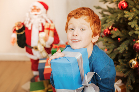 Cute ginger boy embracing christmas gift tightly