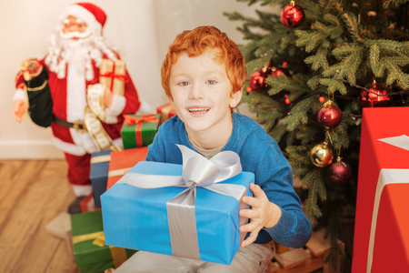 Excited redhead kid smiling while holding his christmas present Stock Photo