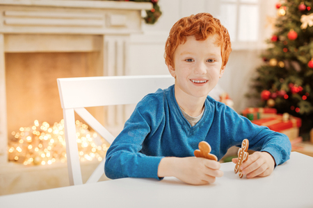 Charming ginger kid smiling while playing with gingerbread men