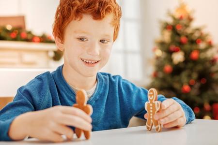 Adorable child smiling while playing with homemade cookies Stock Photo