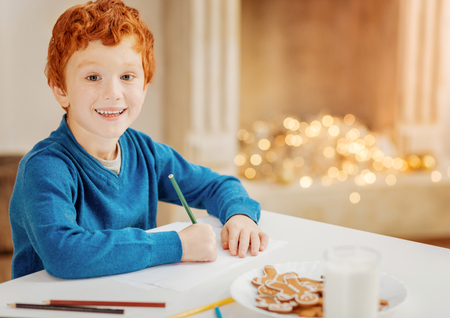 Excited little boy writing letter to santa claus