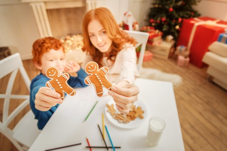 Relaxed family showing gingerbread men into camera