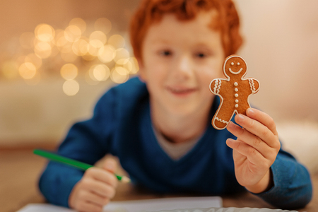 Redhead little boy showing gingerbread man into camera Stock Photo