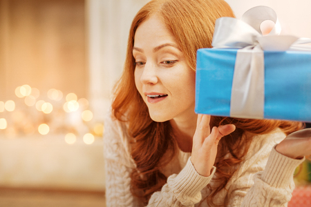 Curious redhead lady guessing what she got for christmas Stock Photo