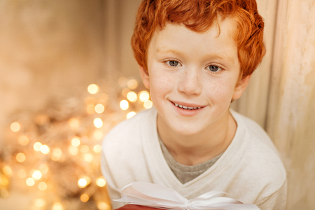 christmastime: Portrait of charming kid smiling while holding gift