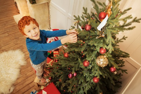 Excited ginger boy decorating christmas tree