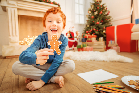 brincando: Excited redhead boy grinning broadly while showing homemade gingerbread man