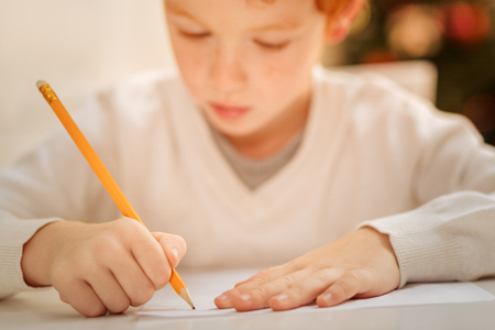 Close up of focused child writing letter to santa claus