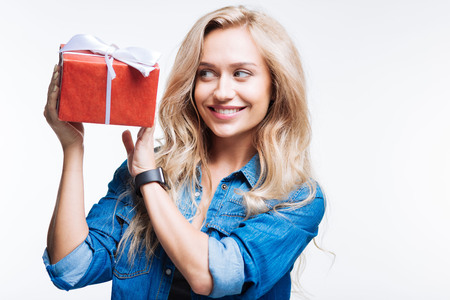 Fair-haired smiling woman holding gift box