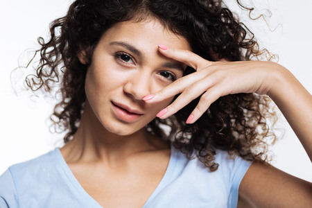 Close up of curly woman posing with fingers near eye