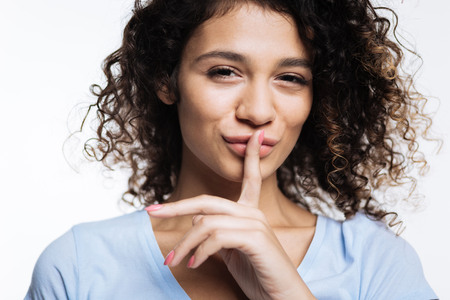 loose hair: Beautiful curly woman pressing fingers to her lips Stock Photo