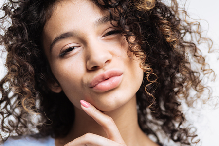 Close up of curly young woman pouting