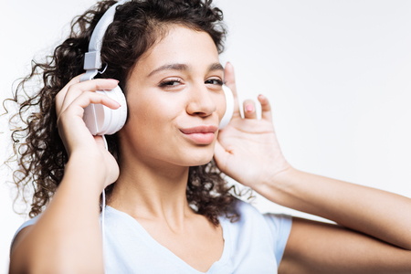 Charming woman listening to music and pouting