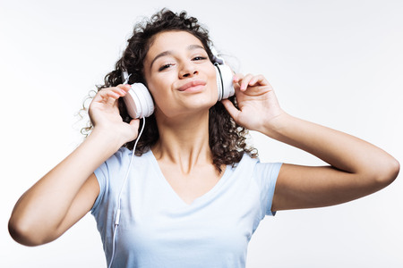 Joyful woman listening to favorite songs and smiling